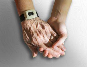 Une main de personne âgée tient celle d'une personne visiblement bien plus jeune