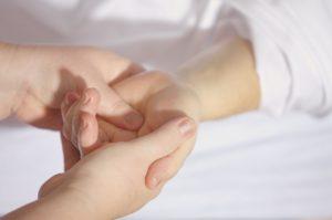 Une main en serre une autre dans un geste de soutien