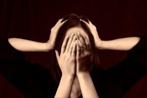 Une femme désespérée dans le noir. Des mains la réconfortent