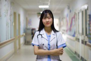 Une soignante en blouse se tient dans un couloir d'hôpital, l'air accueillant.